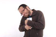 Hombre vestido casual joven que sostiene su smartphone foto de archivo libre de regalías