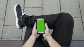 Hombre vestido casual que se sienta en banco en un parque que mira y que usa su smartphone con la exhibición de la croma con la p almacen de metraje de vídeo