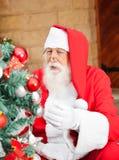 Hombre vestido como Santa Claus Decorating Christmas foto de archivo libre de regalías