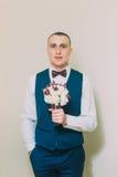 Hombre vestido elegante que sostiene el ramo elegante de rosas que presentan en fondo blanco en blanco fotos de archivo libres de regalías