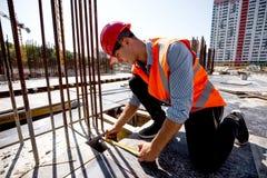 Hombre vestido en camisa, chaleco anaranjado del trabajo y medidas del casco el agujero con una cinta métrica en el solar imágenes de archivo libres de regalías