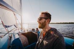 Hombre vestido en ropa de sport y gafas de sol en un yate Retrato barbudo adulto feliz del primer del dueño de un yate Marinero h fotografía de archivo libre de regalías