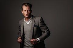 Hombre vestido sostenido confiado en chaqueta gris fotografía de archivo