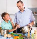 Hombre y adolescente que cocinan junto Imágenes de archivo libres de regalías