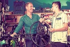 Hombre y adolescente que eligen la nueva rueda Foto de archivo libre de regalías