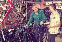 Hombre y adolescente que eligen la nueva rueda Imágenes de archivo libres de regalías