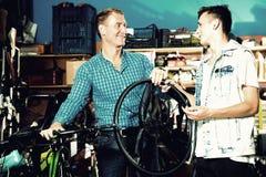 Hombre y adolescente que eligen la nueva rueda Fotos de archivo