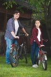 Hombre y adolescente que presentan con las bicicletas en el parque Imagenes de archivo