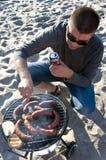 Hombre y barbacoa en la playa Imagen de archivo libre de regalías