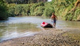Hombre y barco en Jordan River Imagenes de archivo
