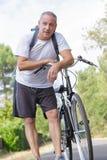Hombre y bicicleta envejecidos centro del retrato imagenes de archivo