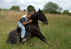 Hombre y caballo que se sienta Imagen de archivo
