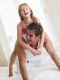Hombre y chica joven en la cama que juega y que sonríe imagen de archivo libre de regalías