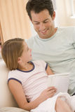 Hombre y chica joven en libro de lectura de la sala de estar Imagen de archivo libre de regalías