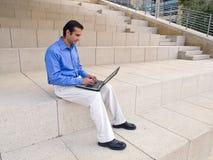 Hombre y computadora portátil en pasos de progresión Foto de archivo