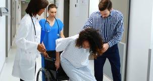 Hombre y doctores que ayudan a la mujer embarazada para sentarse en la silla de ruedas metrajes