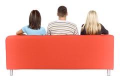 Hombre y dos mujeres en la opinión de la parte posterior del sofá fotografía de archivo