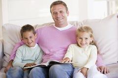 Hombre y dos niños que se sientan en sala de estar Imagenes de archivo