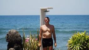 Hombre y ducha en la playa fotos de archivo libres de regalías