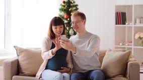 Hombre y esposa embarazada con smartphone en la Navidad almacen de video