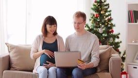 Hombre y esposa embarazada que hacen compras en línea en la Navidad almacen de metraje de vídeo