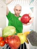 Hombre y frutas en refrigerador Fotos de archivo libres de regalías