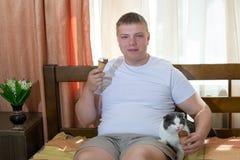 Hombre y gato divertido que comen el cono de helado en la cama Fotos de archivo libres de regalías