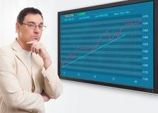 Hombre y gráfico del mercado de acción en la pantalla digital Imagenes de archivo