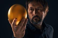 Hombre y huevo de oro foto de archivo libre de regalías