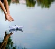 Hombre y las manos y los dos barcos de papel de la mujer fotos de archivo