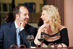 Hombre y muchacha con el vino en el café una fecha Fotos de archivo