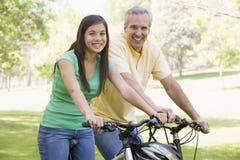 Hombre y muchacha en las bicis al aire libre que sonríen Fotos de archivo libres de regalías