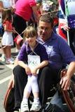 Hombre y muchacha en un sillón de ruedas en carnaval Foto de archivo libre de regalías