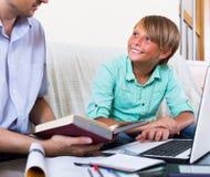Hombre y muchacho adultos con el ordenador portátil dentro Foto de archivo