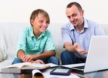 Hombre y muchacho adultos con el ordenador portátil dentro Fotos de archivo libres de regalías