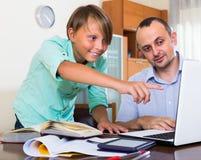 Hombre y muchacho adultos con el ordenador portátil dentro Imagenes de archivo