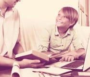 Hombre y muchacho adultos con el ordenador portátil dentro Imagen de archivo libre de regalías