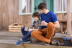 Hombre y muchacho con las tazas del metal de té que se sientan en el pórtico Imagenes de archivo