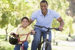Hombre y muchacho joven en las bicis al aire libre que sonríen Foto de archivo