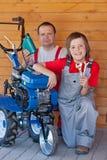 Hombre y muchacho joven que mantienen una pequeña máquina de la sierpe foto de archivo