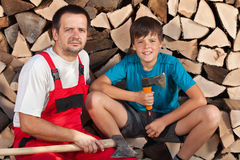 Hombre y muchacho que se sientan junto delante de la madera tajada imagenes de archivo