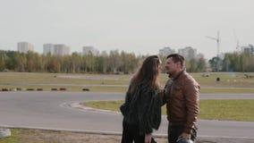 Hombre y mujer alegres en la pista del ir-kart La mujer bonita joven saca su casco protector y besa al hombre almacen de video