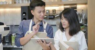 Hombre y mujer asiáticos jovenes del barista dos que usa la tableta durante una rotura en el trabajo en la cafetería almacen de metraje de vídeo