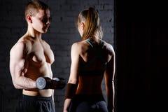 Hombre y mujer atléticos con pesas de gimnasia Foto de archivo