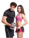 Hombre y mujer atléticos con pesas de gimnasia en el fondo blanco Fotografía de archivo