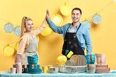 Hombre y mujer atractivos felices en los delantales que se detienen fotografía de archivo libre de regalías
