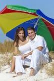 Hombre y mujer bajo el paraguas colorido en la playa Imágenes de archivo libres de regalías