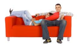 Hombre y mujer cómodos en el sofá anaranjado con el telecontrol Fotografía de archivo libre de regalías
