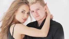 Hombre y mujer cariñosos de los pares, en un fondo blanco en ropa negra almacen de video