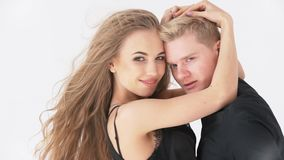 Hombre y mujer cariñosos de los pares, en un fondo blanco en ropa negra metrajes